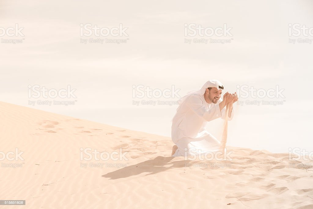 Arab Man Playing with Sand at the Dunes of Dubai stock photo