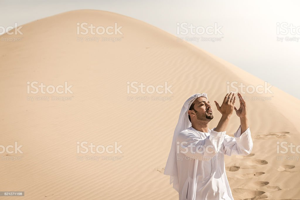 Arab man praying in desert stock photo