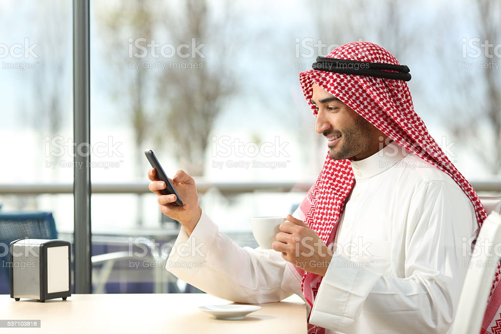 Arab man texting in a smart phone in a bar stock photo