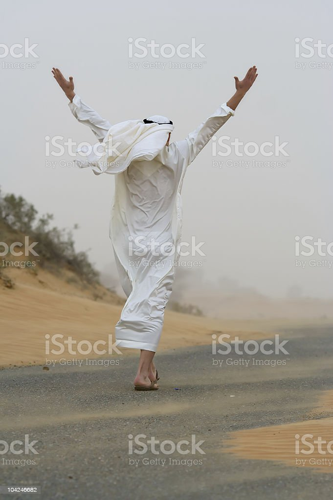 Arab man walking in sand storm royalty-free stock photo