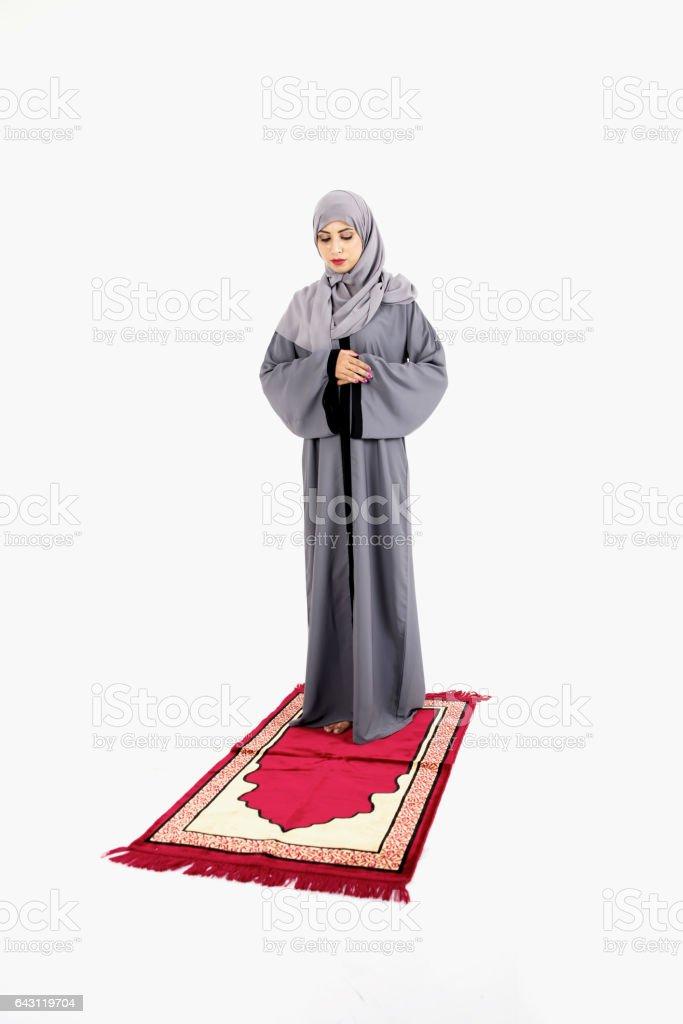 Arab Muslim woman praying on a praying carpet stock photo
