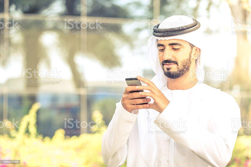 Arab National woking on his smartphone stock photo