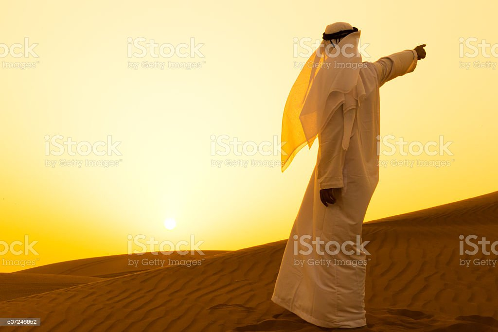 Arab pointing at a direction in the dunes of Dubai stock photo