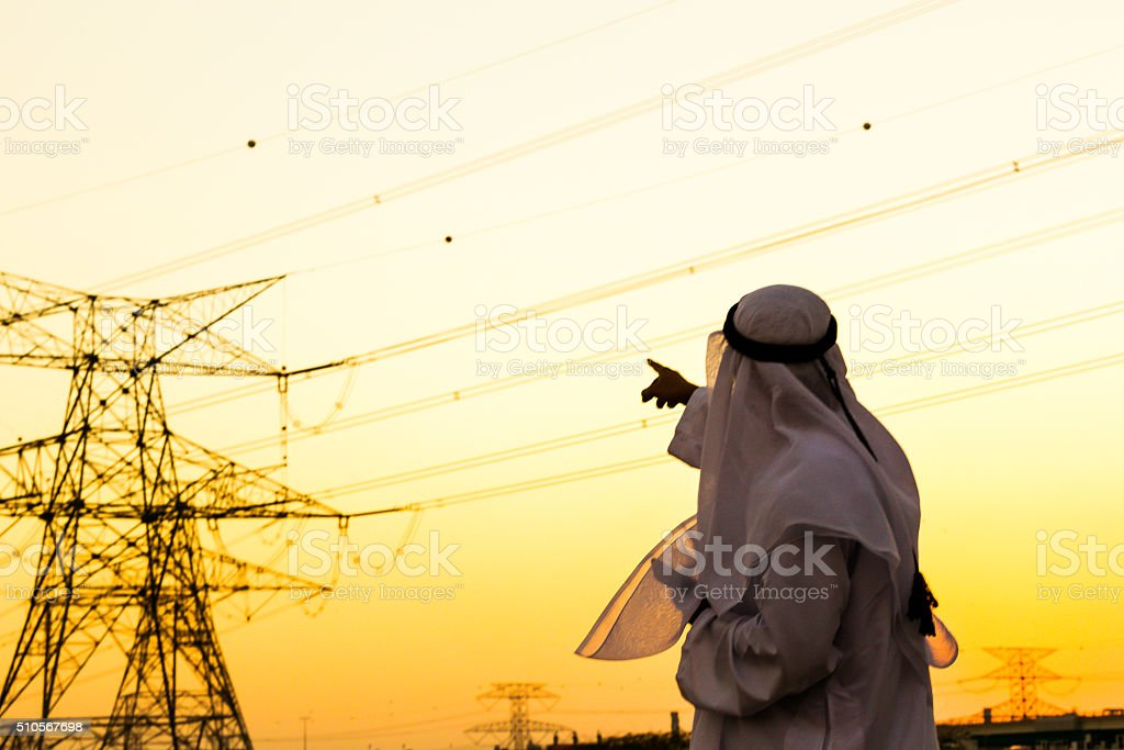 Arab pointing towards Electrical Pylon stock photo