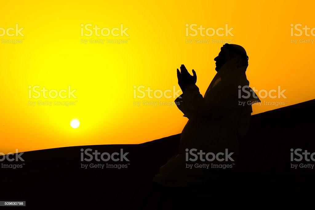 Arab praying in the desert stock photo