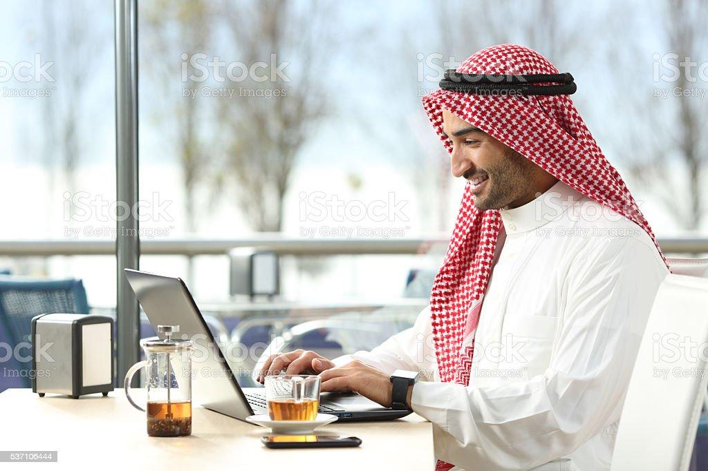Arab saudi man working online with a laptop stock photo