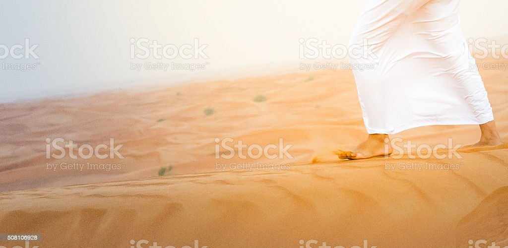 Arab walking during windy dry climate in a desert dune stock photo