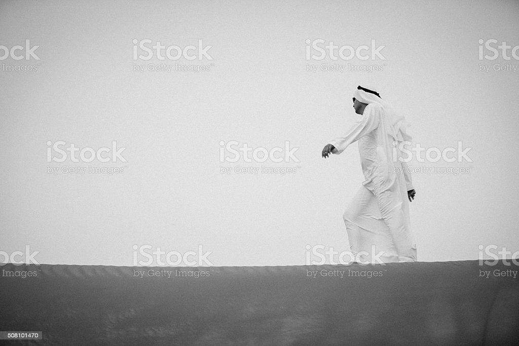 Arab Walking on the Edge of Sand Dunes stock photo