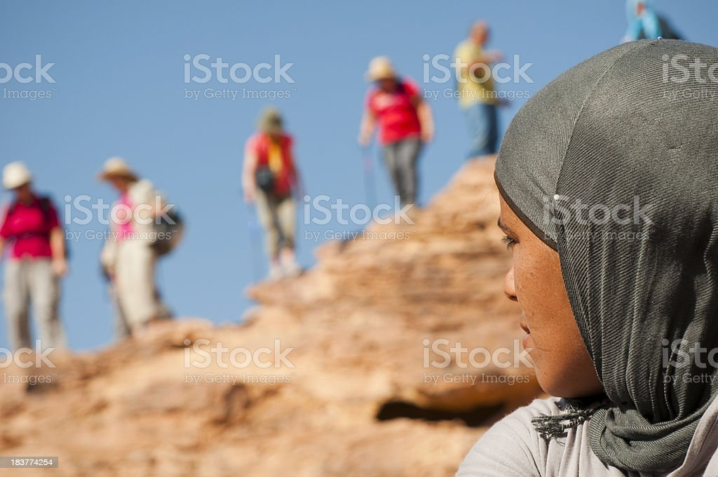Arab woman and tourists in Petra, Jordan royalty-free stock photo