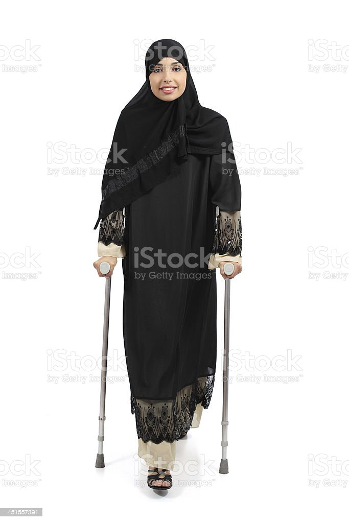Arab woman walking with crutches stock photo