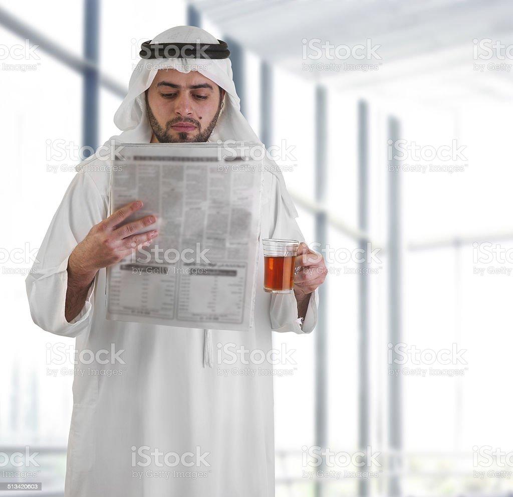 arabian business man in office drinking tea reading news stock photo