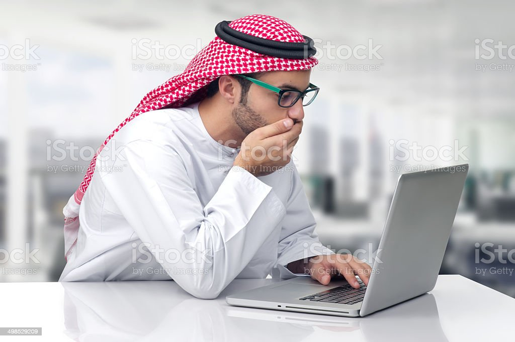 Arabian business man looking shocked at his computer stock photo