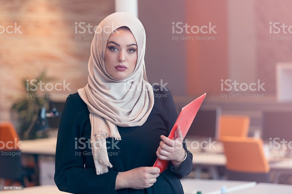 Arabian business woman holding a folder in modern startup office stock photo
