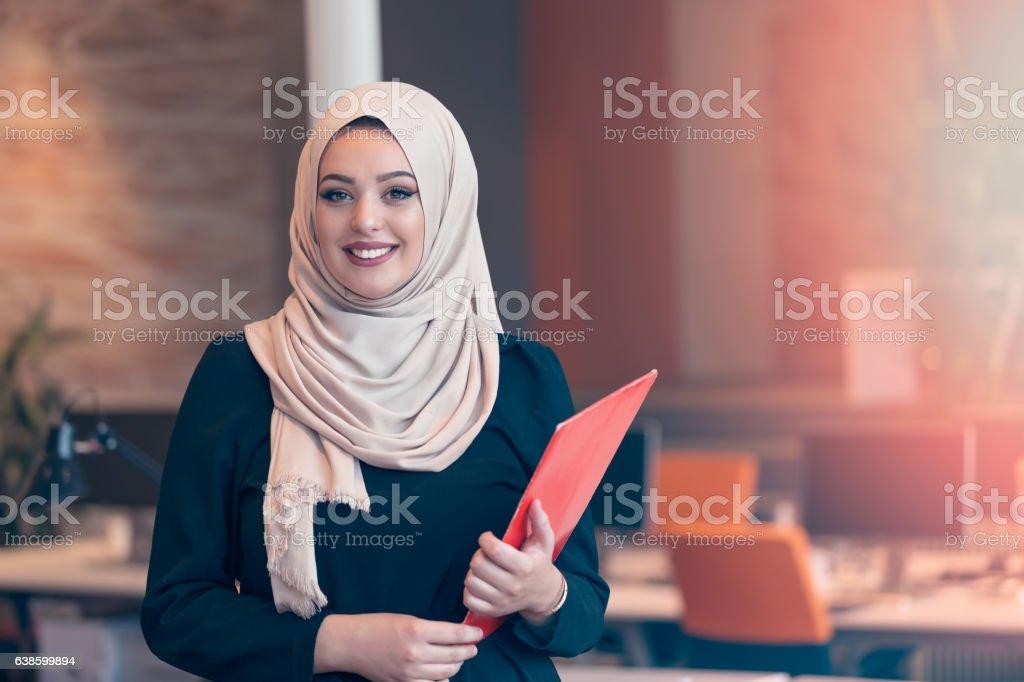 Arabian business woman holding a folder in modern startup office stock photo
