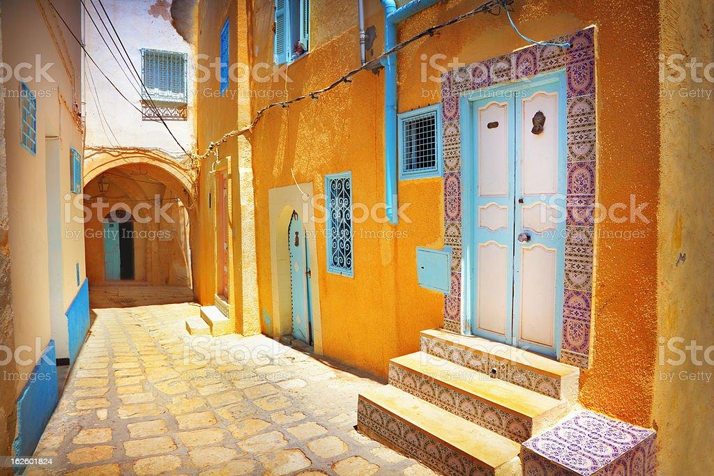Arabian cobblestone street with orange colored building stock photo