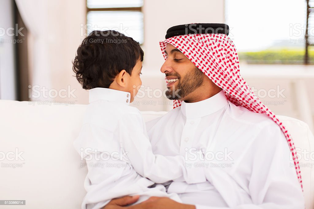 arabian father and son sitting at home stock photo