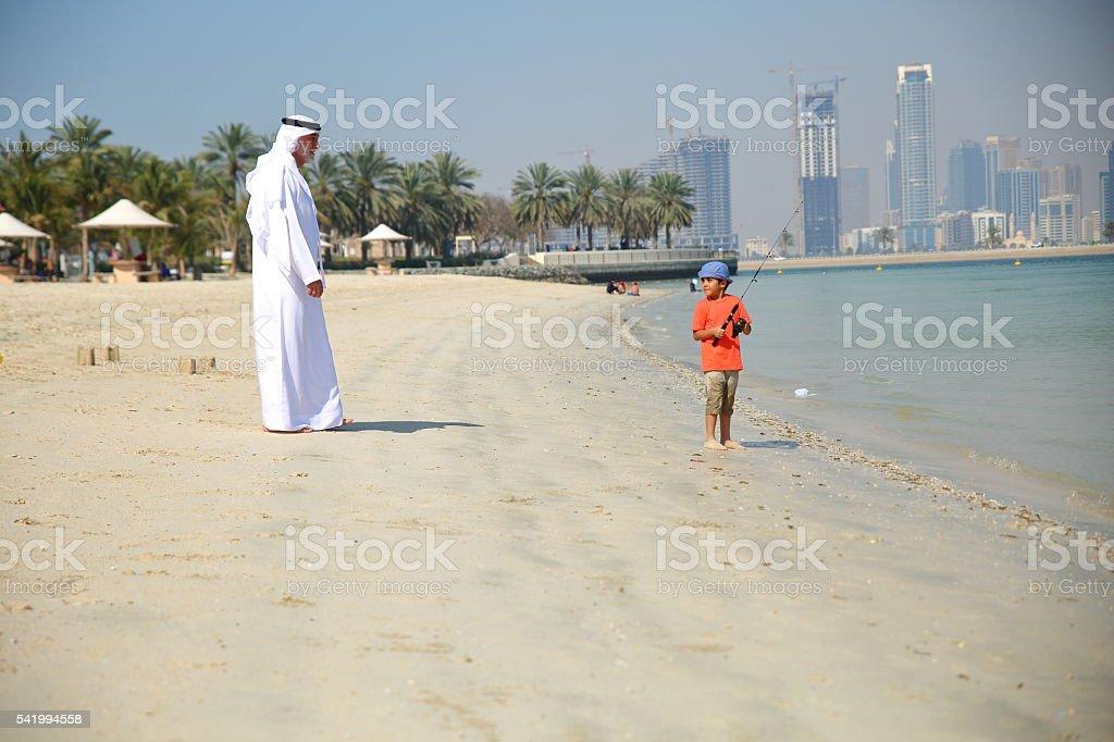 Arabian Grandfather and grandson fishing together on sea. stock photo