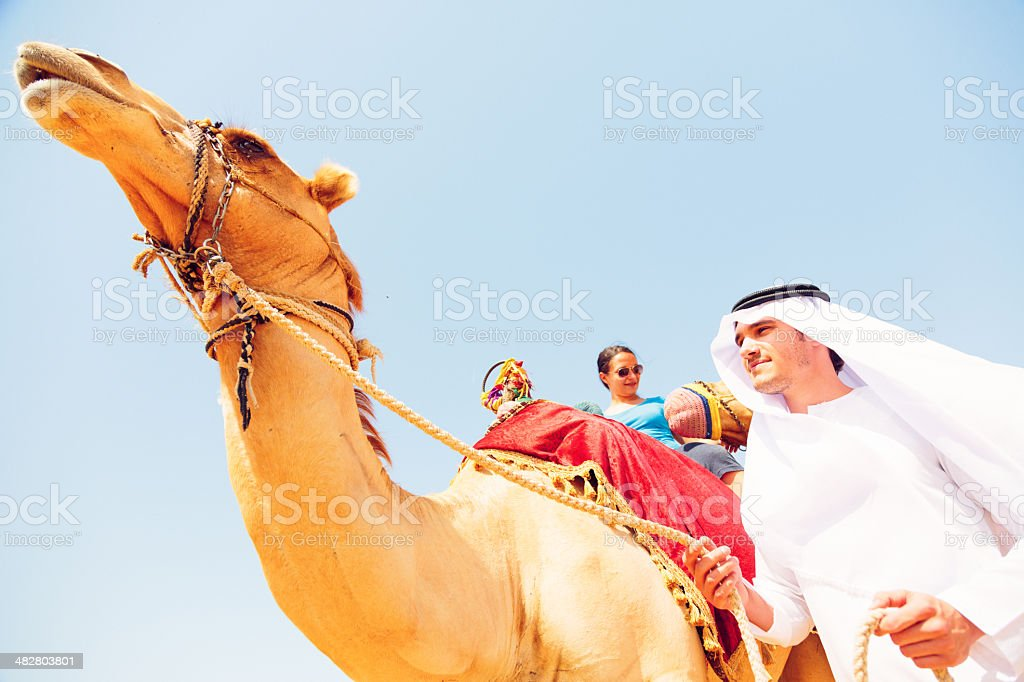 arabian man and tourist riding a camel royalty-free stock photo