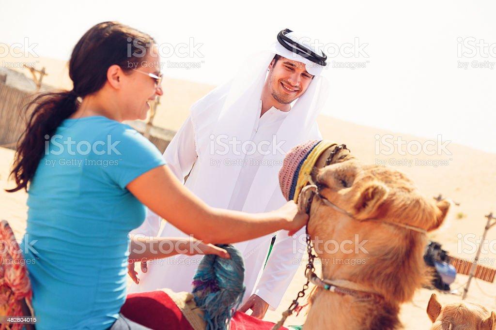 arabian man and tourist riding a camel royalty-free stock photo