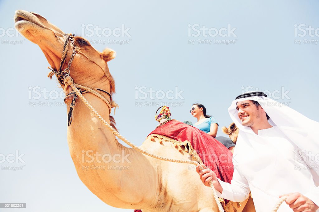 arabian man and tourist riding a camel stock photo