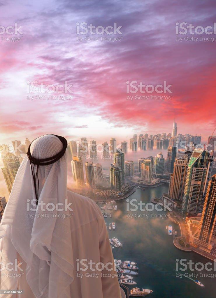 Arabian man is watching Dubai marina in Dubai, United Arab Emirates. stock photo