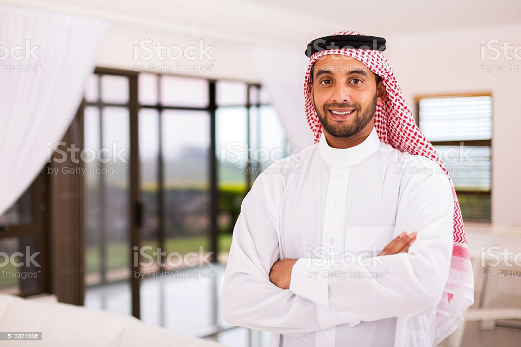 arabian man standing indoors stock photo