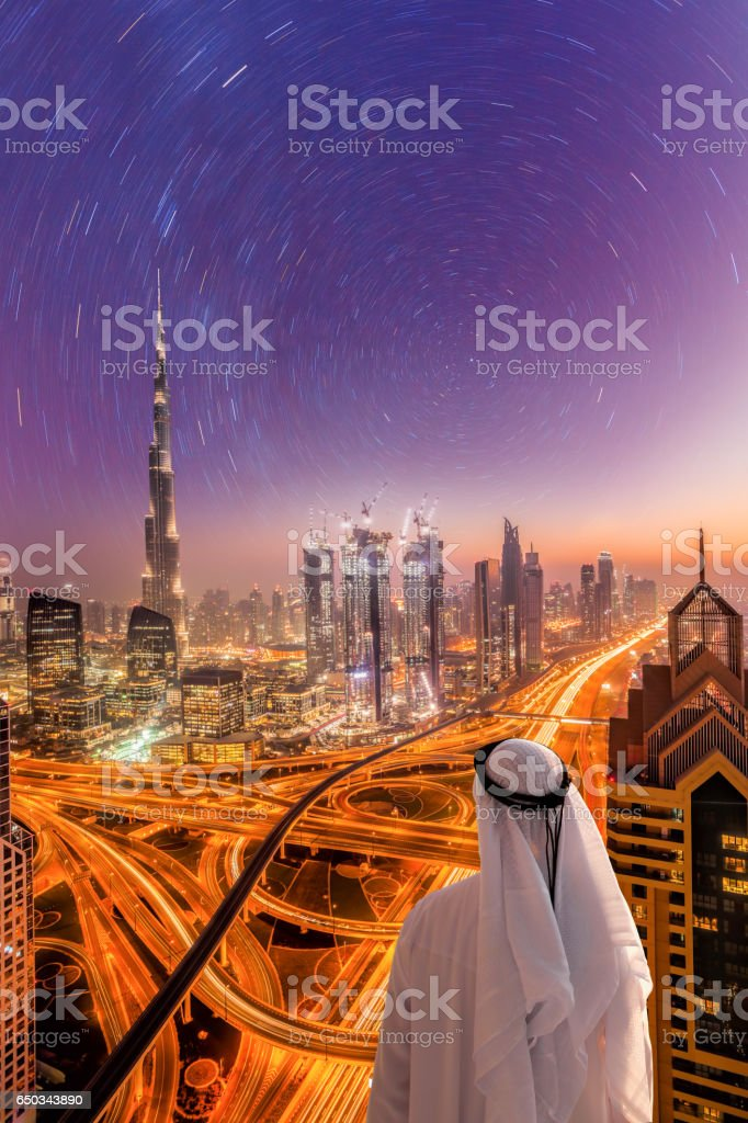 Arabian man watching night cityscape of Dubai under a starry sky in United Arab Emirates stock photo