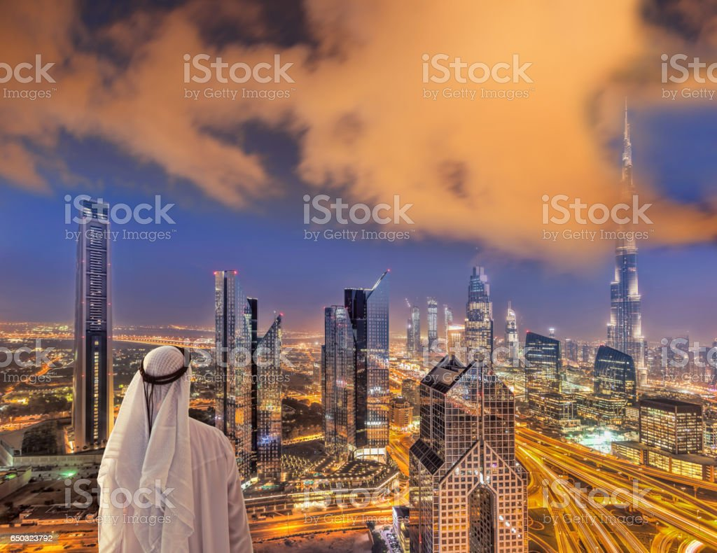 Arabian man watching night cityscape of Dubai with modern futuristic architecture in United Arab Emirates stock photo