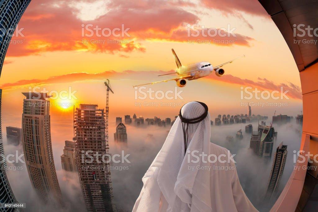 Arabian man watching plane flying over Dubai in United Arab Emirates stock photo