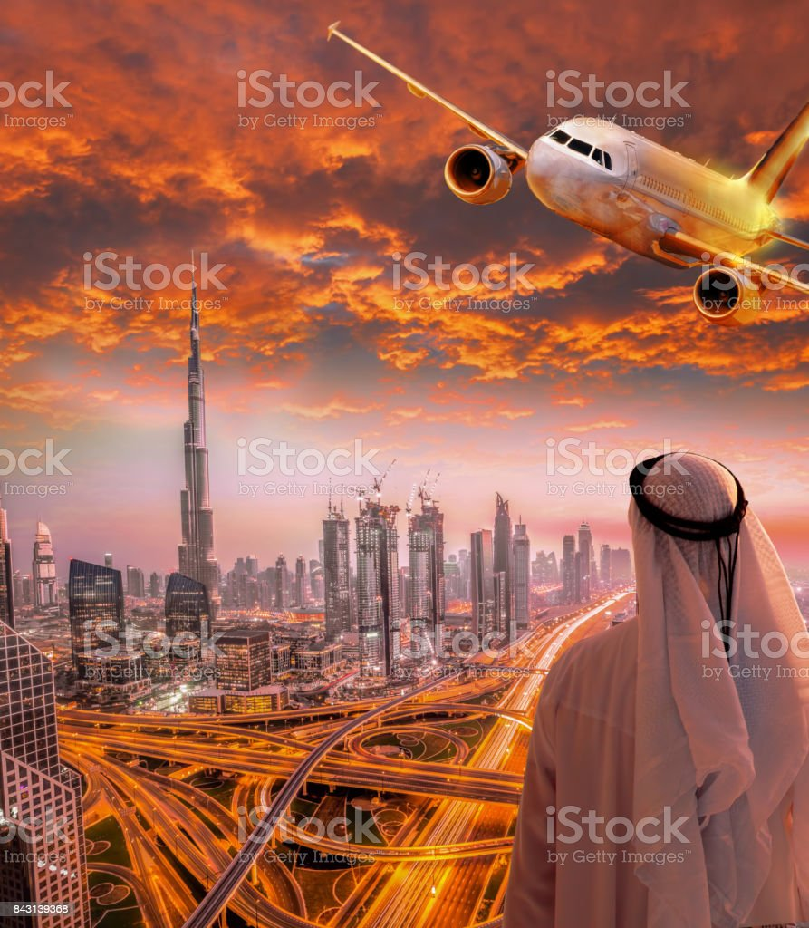 Arabian man with airplane flying over Dubai against colorful sunset in United Arab Emirates stock photo