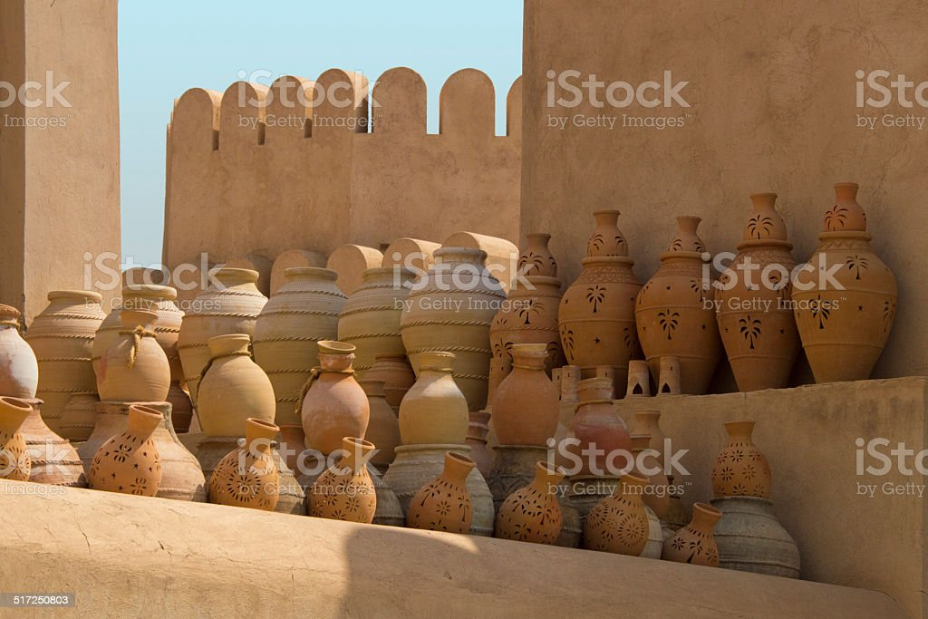 Arabian pottery standing against an old wall stock photo