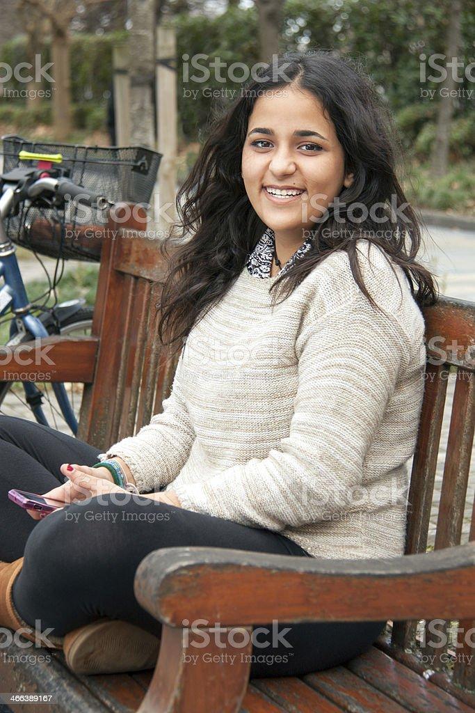 Arabian teen girl with smart phone outdoors stock photo