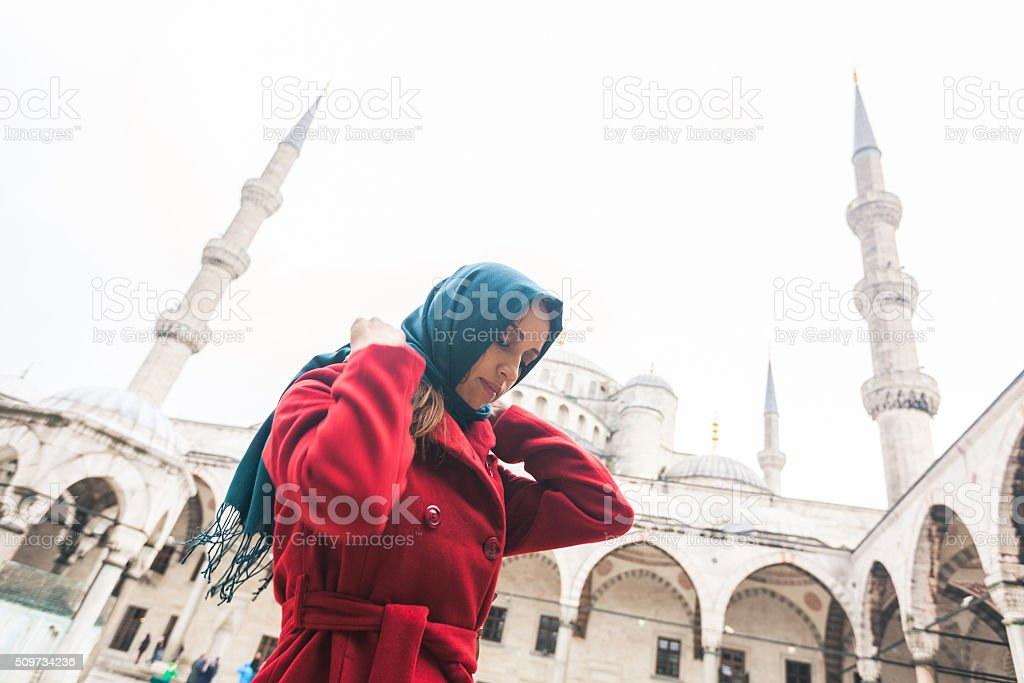 Arabian woman wearing veil in front of a mosque stock photo