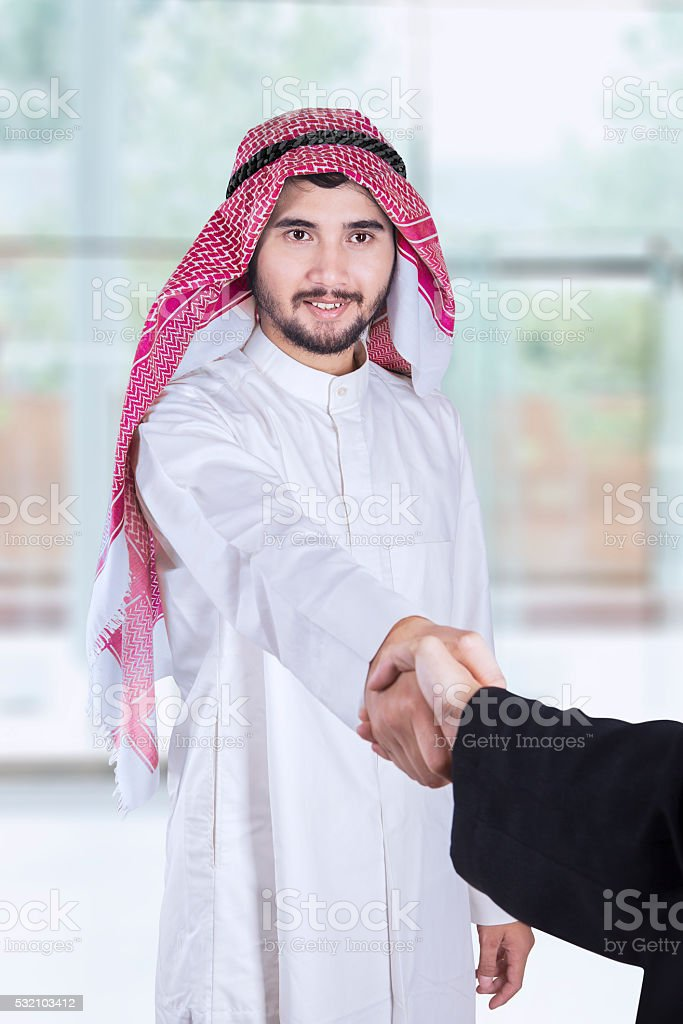 Arabian workers shaking hands in office stock photo