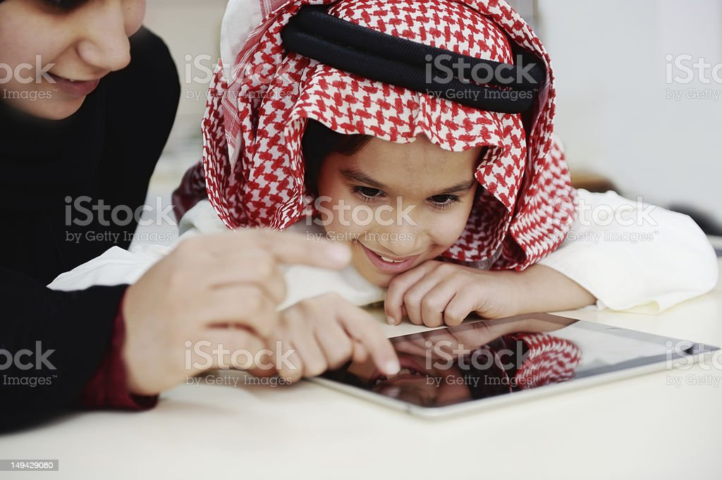 Arabic little boy and his mother working with touch tablet royalty-free stock photo