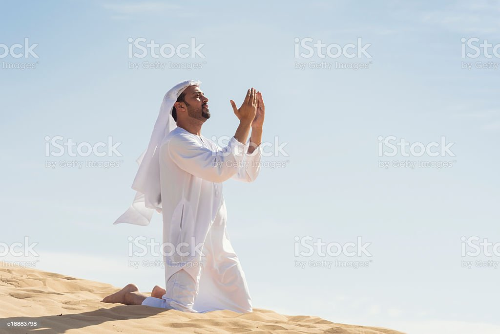 Arabic man praying in the desert stock photo