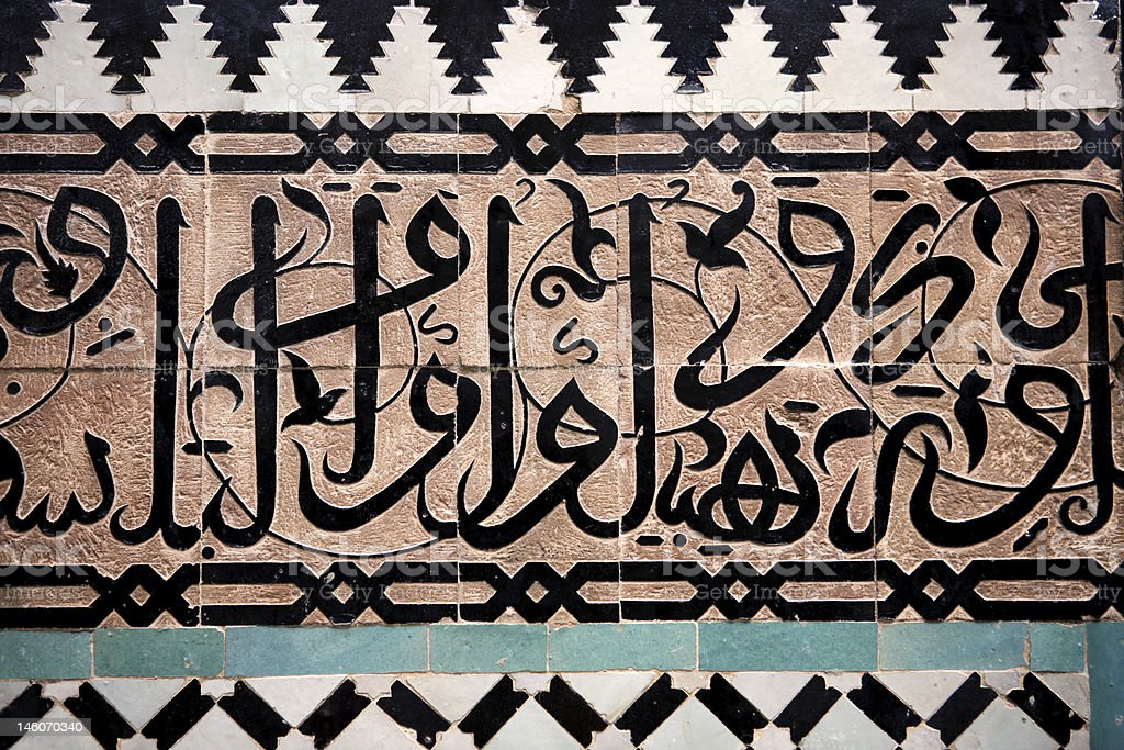 Arabic script on tiled wall in black, white, tan, and Aqua stock photo