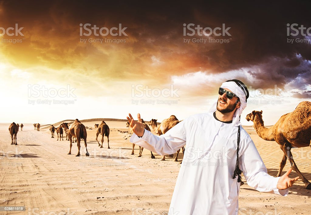 arabic sheik on the desert walking with the camel stock photo