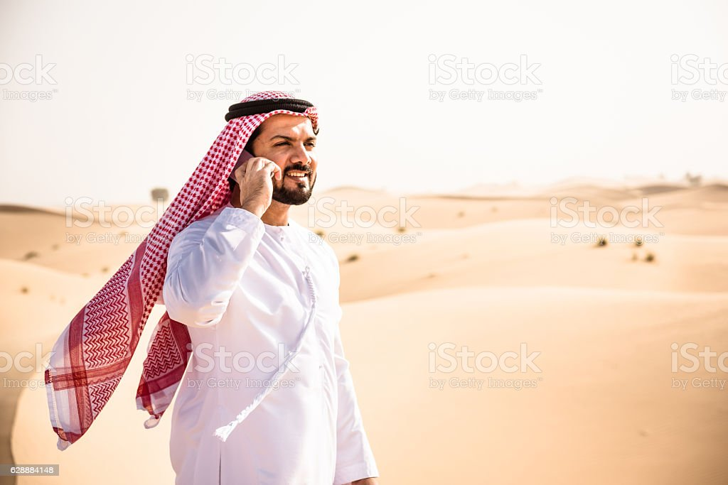 arabic sheik on the phone on the desert stock photo