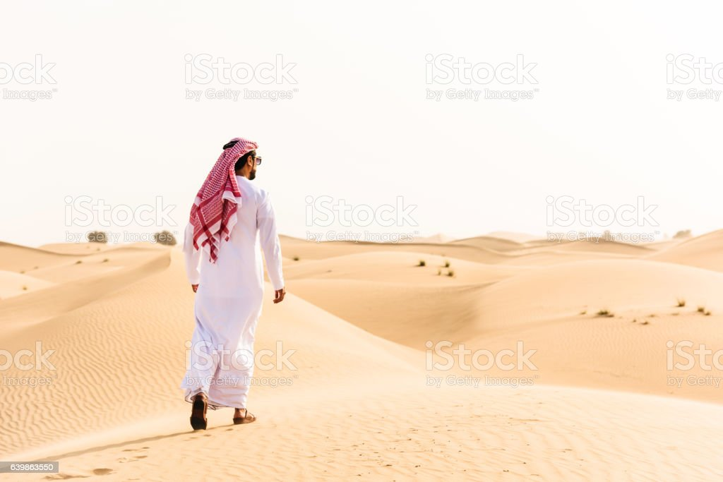 arabic sheik walking on the desert stock photo
