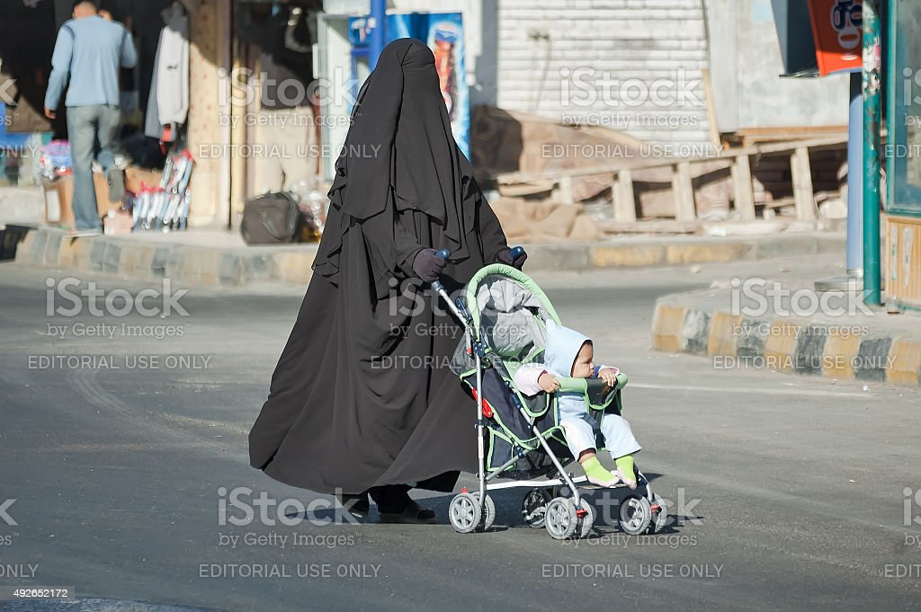Arabic woman in hijab conducts carriage with child stock photo