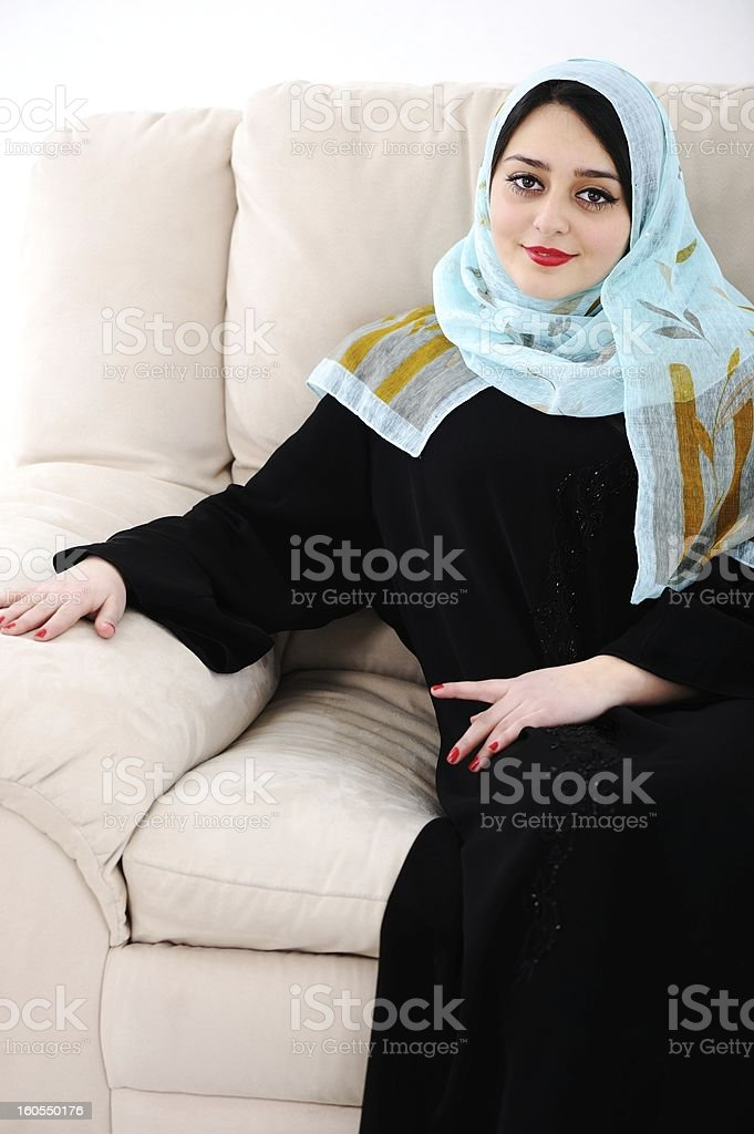 Arabic woman sitting on sofa at home royalty-free stock photo