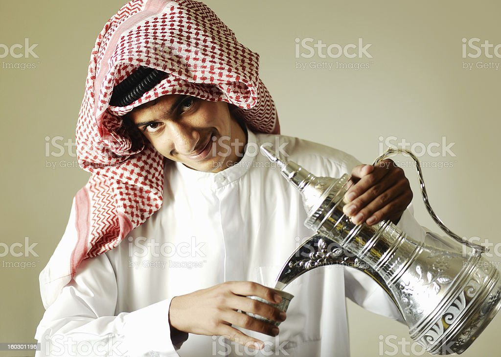 Arabic young man pouring a traditional coffee royalty-free stock photo