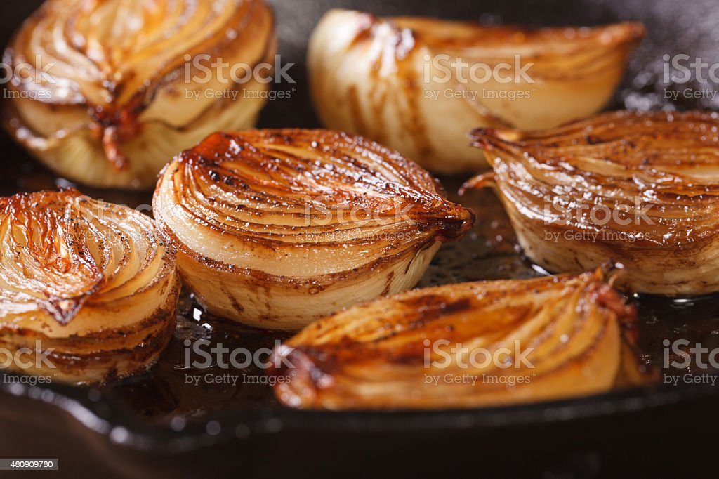 ?aramelized onion halves with balsamic vinegar in a pan stock photo