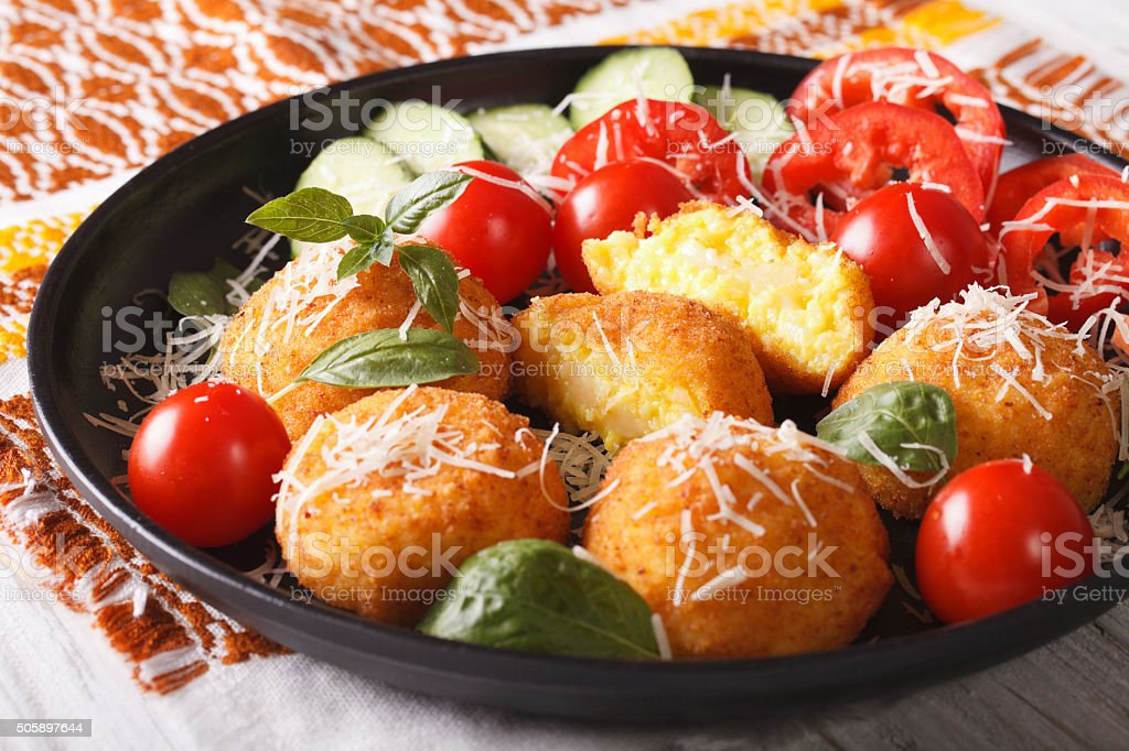arancini rice balls with vegetables close-up on a plate. Horizon stock photo