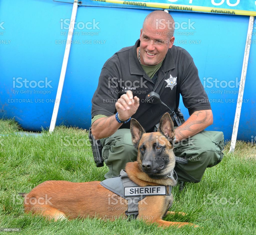 Araphoe County Sherrif with K-9 dog speaking to the crowd stock photo