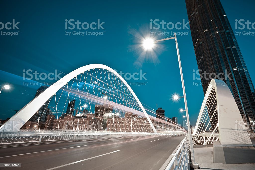 Arc bridge girder highway car light trails city night landscape stock photo
