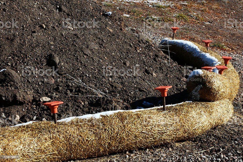 Arc of Fiber Rolls keeping black soil from eroding stock photo