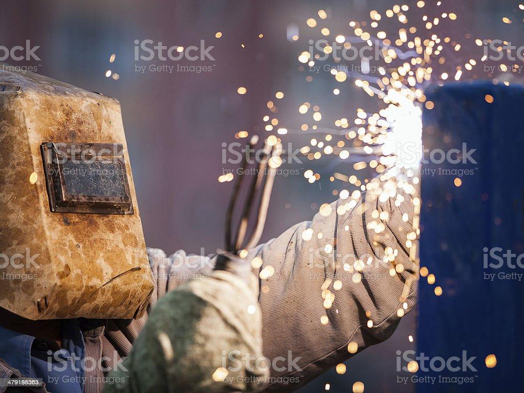 Arc welder worker in protective mask welding metal construction stock photo
