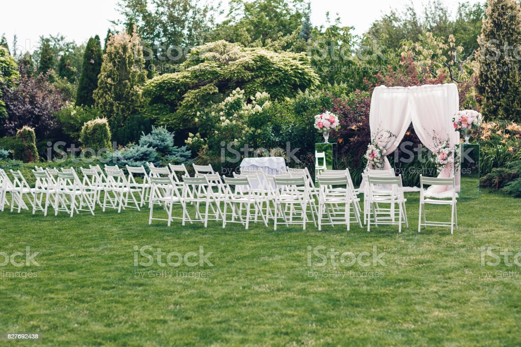 Arch and chairs for the wedding ceremony, decorated with cloth and...